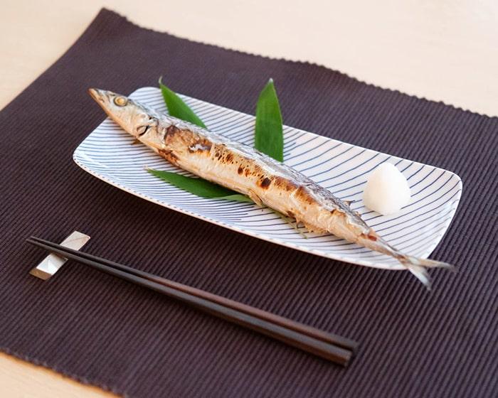 重ね縞に秋刀魚を乗せると少しお皿からはみ出ている