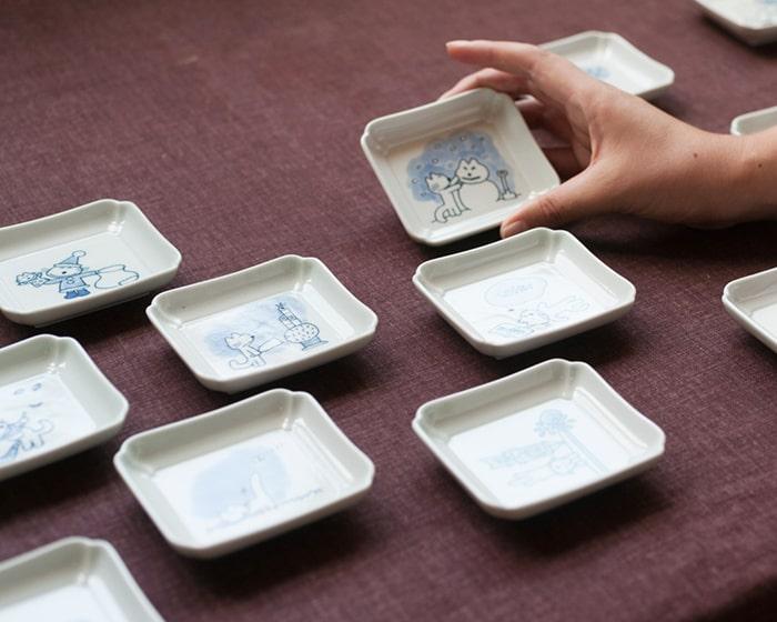 ランダムに並んだ東屋11匹のねこ豆皿の1つを手にとっている