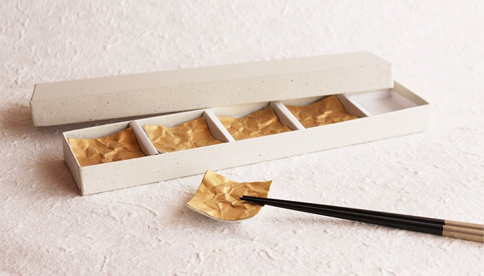 クリンクル金の箸置きが4つ箱の中に入っていて1つに箸を乗せている様子
