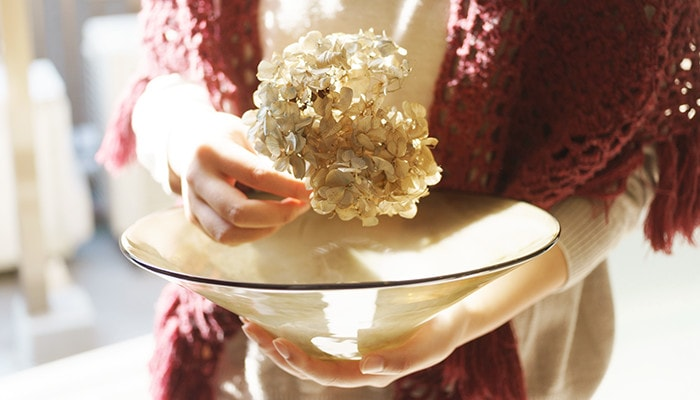 A woman has dried hydrangea and glass bowl of kasumi from fresco