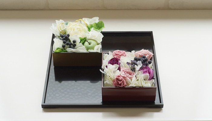 2 Jubako boxes filled with flowers on a serving tray