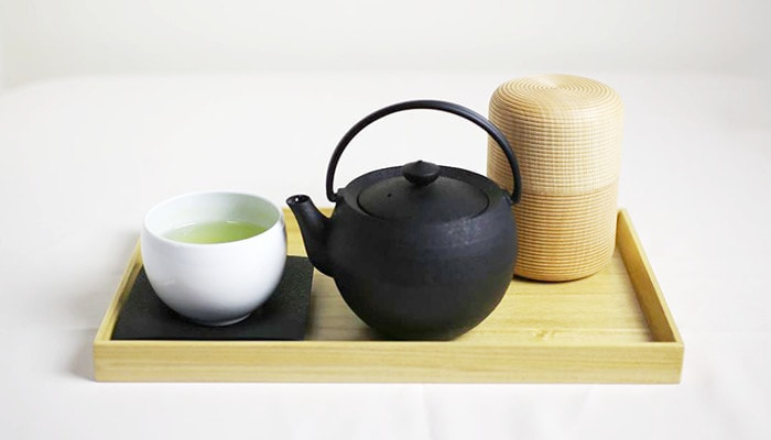 Japanese green tea in yunomi, cast iron teapot of Chushin Kobo and wooden tea canister Karmi of Gato Mikio
