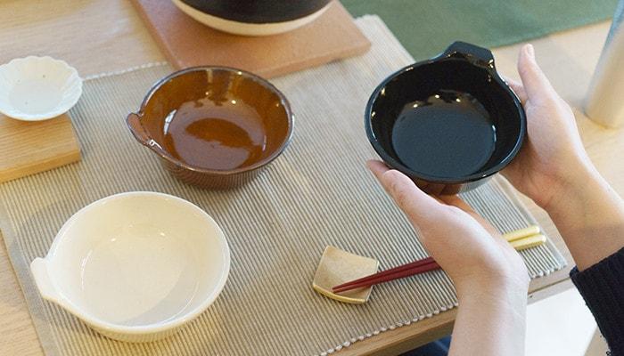 テーブルにアグラとんすいが並んでいて、1つを女性が手に持っている