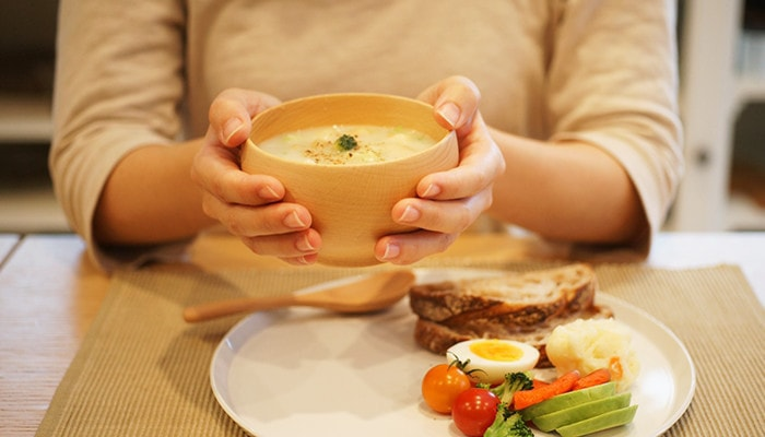 スープが入った薗部産業のめいぼく椀を女性が持っている