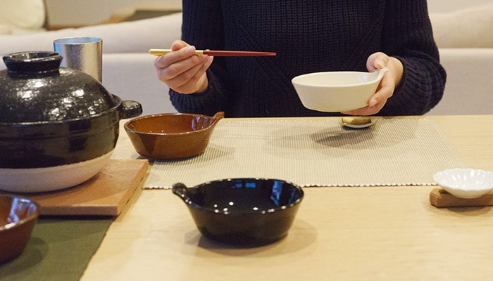 テーブルにアグラとんすいや炊飯土鍋が並んでいて、女性がとんすいと箸を持っている