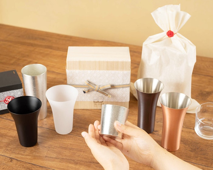 Various unique drinking glasses in Japan Design Store and a woman has tin tumbler