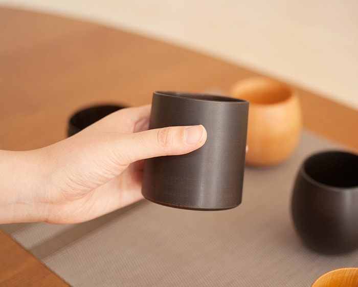 A woman has Black wooden cup SAKURA Cylinder from Gato Mikio