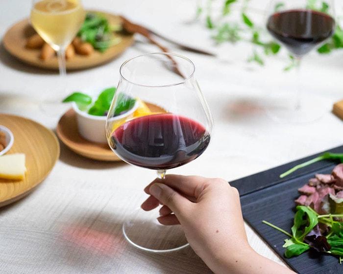 ワインが注がれたワイングラスを手に持っている