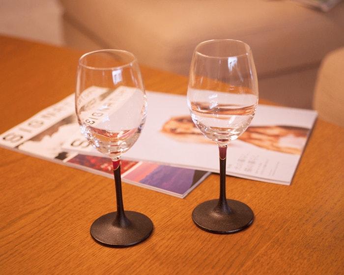 テーブルに2つのうるしのワイングラスと雑誌が置かれている