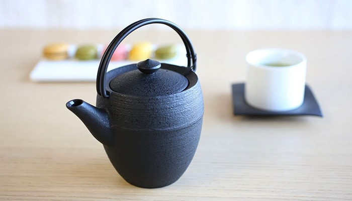 There are a cast iron teapot, a teacup with Japanese green tea, and a macaroon on a aplate.
