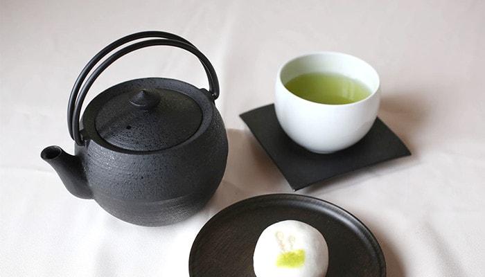 鋳心ノ工房のティーポットとお茶の入った湯呑みと和菓子