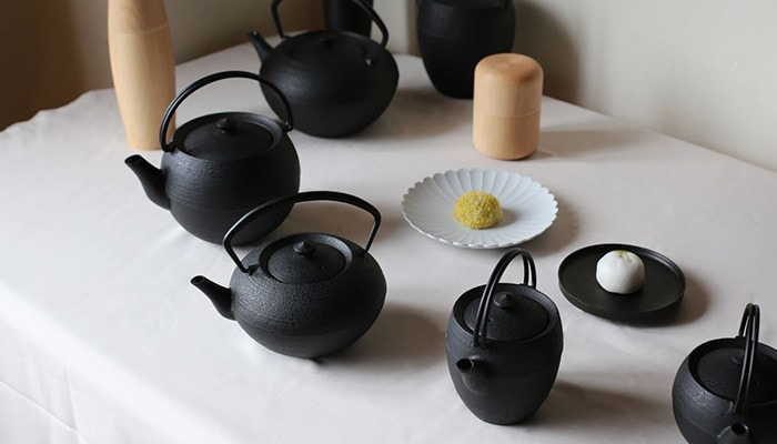 There are a cast iron teapot beside a wooden tea canister Karmi.