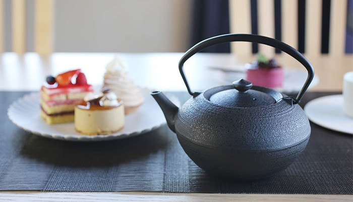 These are a cast iron teapot and some petit cakes on a Palace plate.