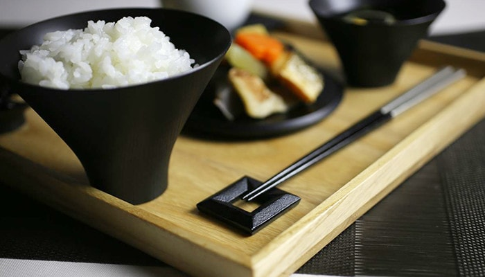 Thies is a table coordinate of a set meal with cast iron chopstick rest on a wooden tray.