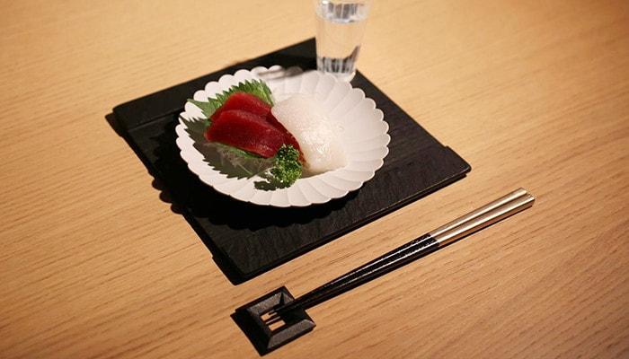 中央にはSUZURIの上にお刺身が乗ったパレスプレートを乗せて、手前には鋳心ノ工房の箸置きと箸がセットされた食事の様子